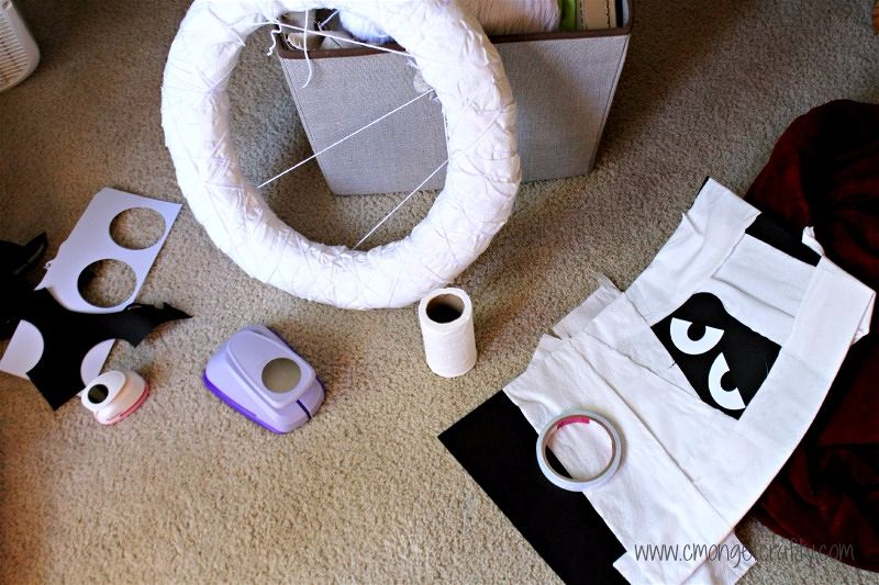 Use toilet paper, paper, and yarn to make your own DIY Toilet Paper Mummy wreath! #halloween #diy #mummywreath #diyhalloweendecor #notsoscaryhalloween #cheapcrafts #toiletpapermummywreah #diyhalloween #diywreath #mummy #mummywreath #halloweendoor #cmongetcrafty