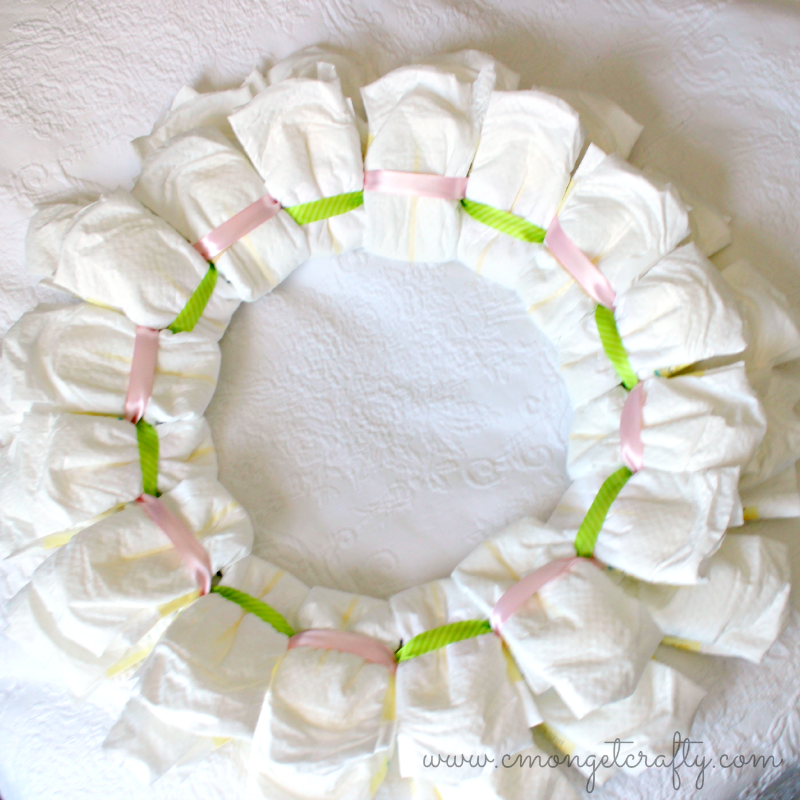 Make a Diaper Wreath for the next baby shower you host! Some ribbon and decos and this baby shower diaper wreath is ready to go! #babyshower #diaperwreath #newbaby #diy #party
