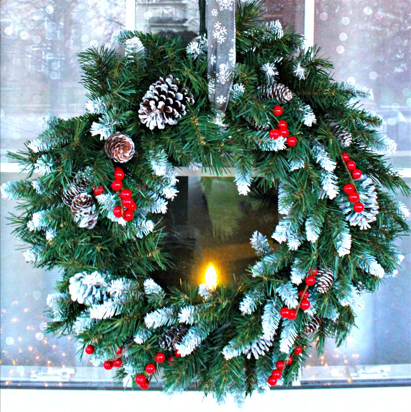Add a touch of wintry elegance to your front porch decor with a beautiful wreath hung by ribbon over your window!