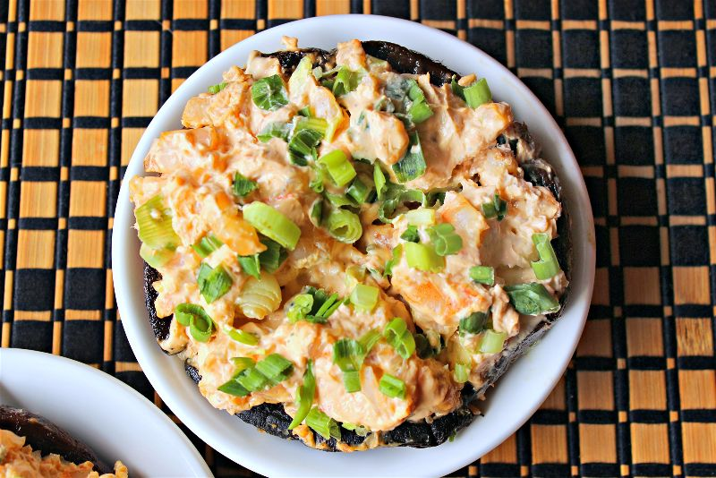 These creamy shrimp and salmon stuffed mushrooms are filling and tasty, and go a long way in large portabella mushroom caps! Top with green onions for color and crunch!